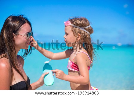 Little girl gets sun cream on her mother's nose - stock photo