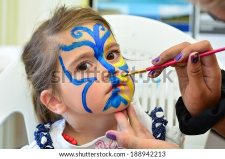 Little girl getting her face painted in butterfly shape by face painting artist. Make up.  - stock photo