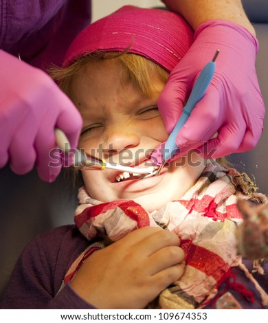 Little girl getting her teeth checked at the dentist - stock photo