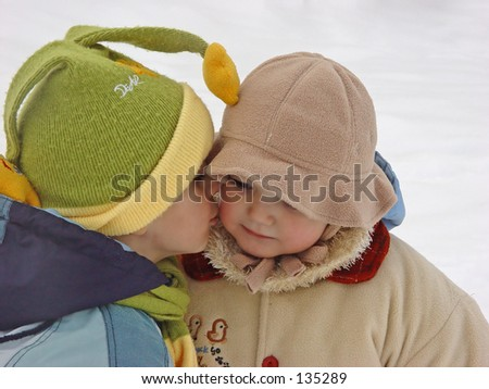 little girl getting kissed by little boy - stock photo