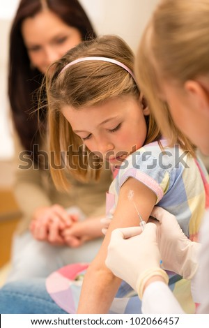 Little girl getting vaccination from pediatrician at medical office - stock photo