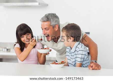 Little girl giving cereal to her father with brother smiling in kitchen - stock photo