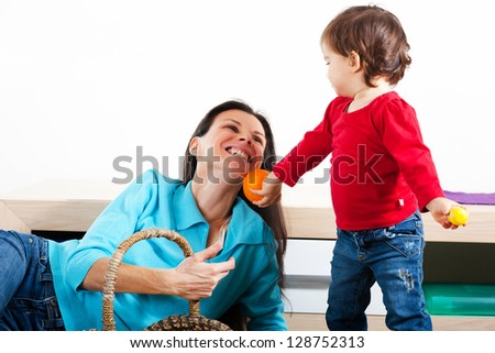Little girl giving her mother an orange - stock photo