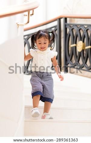 Little girl going downstair - stock photo