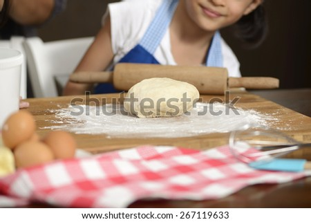 Little girl hand making dough on the wooden table - stock photo