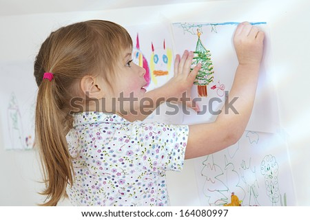 Little  girl hanging her picture proudly  - stock photo