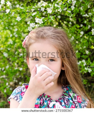Little girl has allergy to spring blossoming and blowing her nose outdoor - stock photo