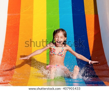 Little girl has into pool after going down water slide during summer  - stock photo
