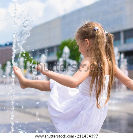 Little girl have fun in open street fountain at hot summer day - stock photo