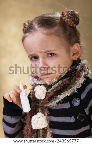 Little girl having a cold holding a nose spray - stock photo