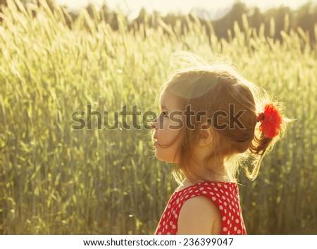 Little girl having fun at sunset - stock photo