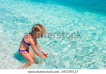 Little girl having fun on tropical beach eith turquoise ocean water - stock photo