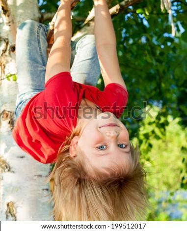 Little girl having fun playing on birch tree - stock photo