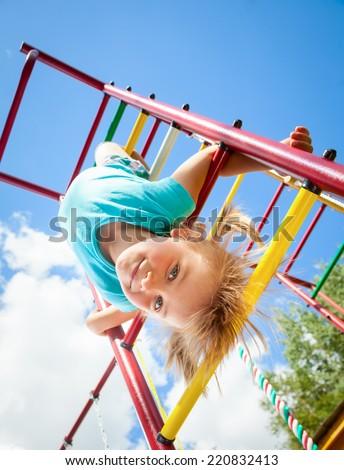Little girl having fun playing on monkey bars - stock photo