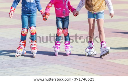 Little girl having fun roller-skating in the street - stock photo