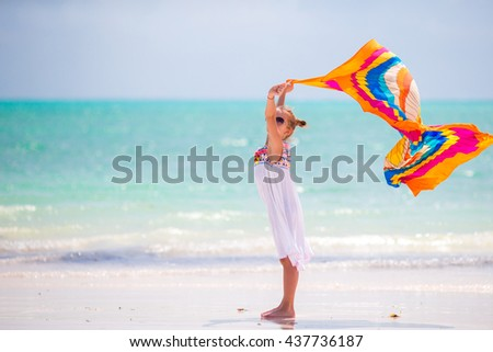Little girl having fun running with pareo on tropical beach - stock photo