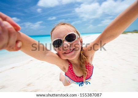 Little girl having fun with her dad at beach - stock photo
