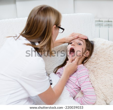 little girl having his throat examined by health professional - stock photo