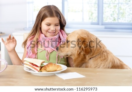 Little girl having lunch at table, smiling dog sitting by her side. - stock photo