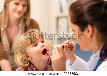 Little girl having throat examination by pediatrician using light pen - stock photo
