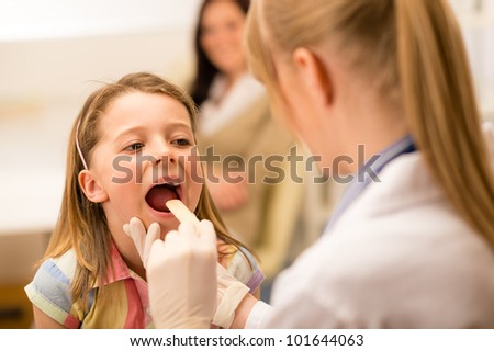 Little girl having throat examination with tongue depressor - stock photo