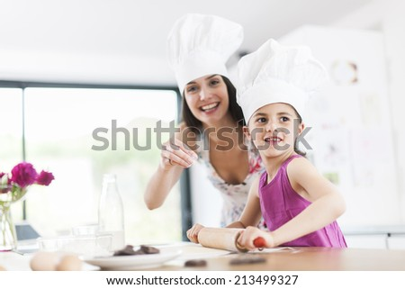 little girl helping her mother prepare a cake - stock photo