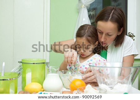 little girl helping her mother to bake a cake - stock photo
