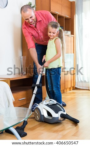 Little girl helping man to do regular clean-up indoors - stock photo