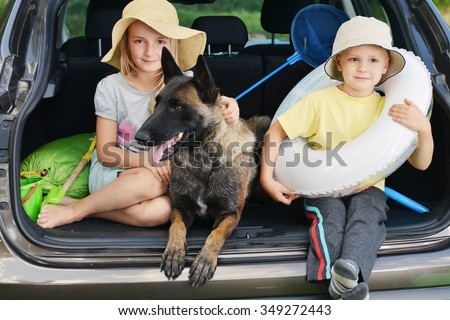 little girl , her brother and dog sits in car  - stock photo