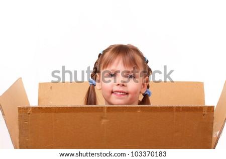 Little girl hiding in cardboard box - stock photo