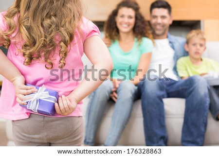 Little girl hiding present from her family behind back at home in living room - stock photo