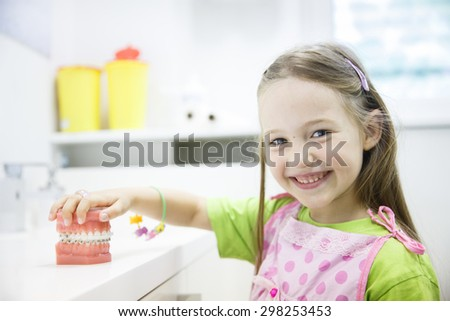 Little girl holding an artificial model of human jaw with dental braces in orthodontic office, smiling. Pediatric dentistry, aesthetic dentistry, early education and prevention concept.   - stock photo