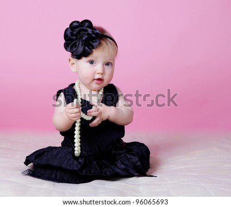 Little girl holding beads in hands - stock photo
