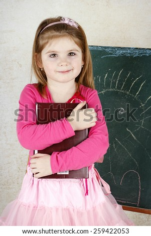 Little girl holding book and standing in front of the blackboard - stock photo