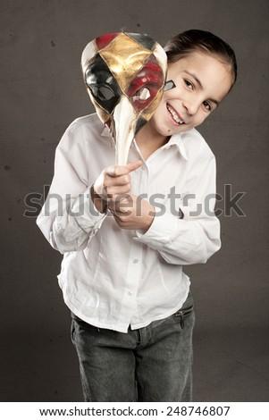 little girl holding carnival mask - stock photo