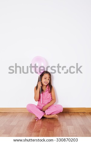 Little girl holding color balloons with gray background - stock photo