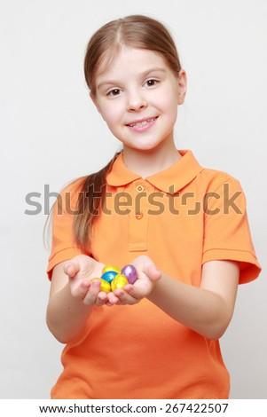 Little girl holding colorful Easter eggs - stock photo