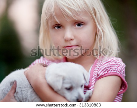 Little girl holding cute small puppy. Summer day. Sunset. - stock photo