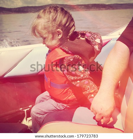 Little girl holding daddies hand in boat with instagram effect - stock photo
