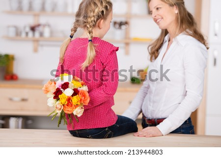 Little girl holding flowers behind her back by her mother on mother's day at home - stock photo