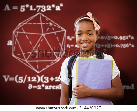 Little girl holding folders in school corridor against desk - stock photo