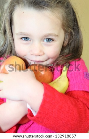 little girl holding fruits in her arms - stock photo