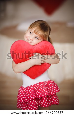 Little girl holding heart-shaped pillow. Valentines day. Mothers day - stock photo