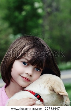 Little girl holding her puppy, an English Cream Labrador Golden retriever mix. - stock photo