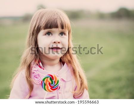 little girl holding lollipop in her hand - stock photo
