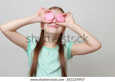 Little girl holding macaroons - stock photo