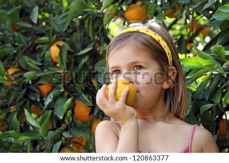 Little girl holding orange - stock photo
