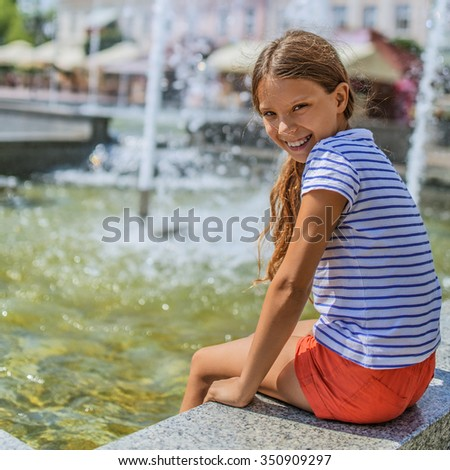 Little girl holds legs over fountain and laughs. - stock photo