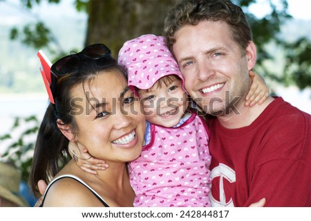 Little girl holds mommy and daddy really tight! - stock photo