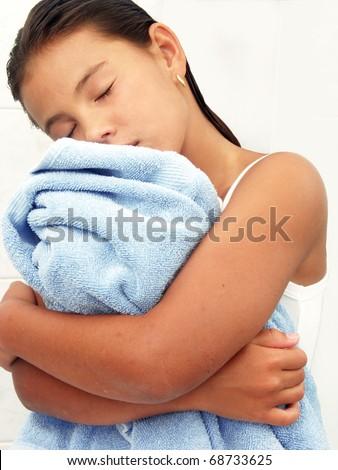 Little girl hugging a blue towel. - stock photo